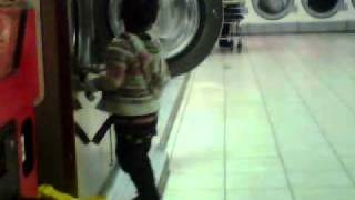 Funny little kids getting in the washing maching at the washateria
