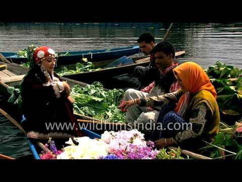 Beautiful Kashmiri girls sell fresh flowers and vegetables on boats in Srinagar, India