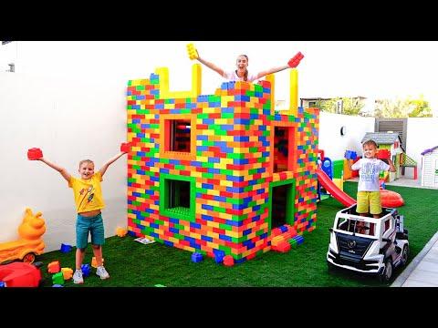 Vlad et Niki jouent avec des blocs de jouets colorés et construisent une maison à trois niveaux