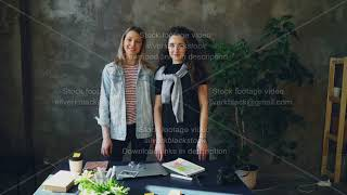 Two young female business colleagues are standing together in loft style office, posing and looking