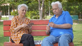Old Indian couple playing card games while sitting on a park's bench - leisure time