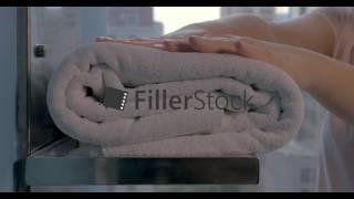 Housekeeper placing bath towels in hotel bathroom