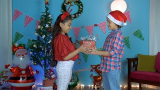 Cute little boy gifting his pretty sister a special Christmas present in India