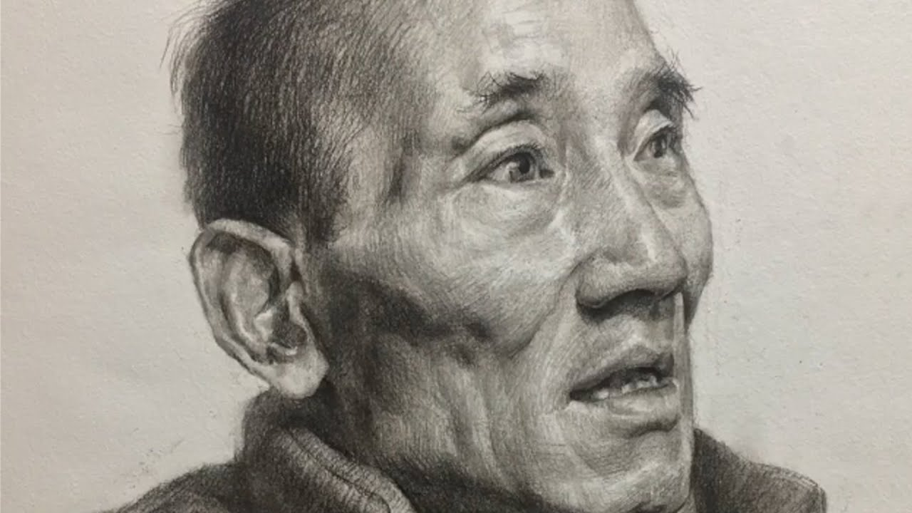 Drawing a portrait of man with charcoal pencil