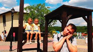 Папа и девочки веселятся вместе в парке аттракционов