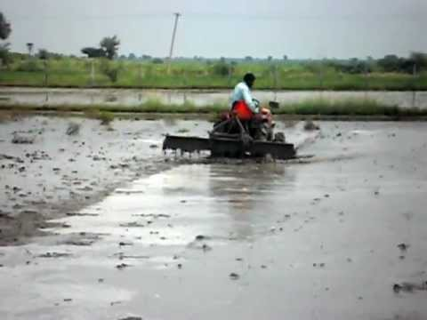 KUBOTA B2420 TRACTOR WITH LEVEL BLADE WORKING IN PADDY FILED IN BELLARY