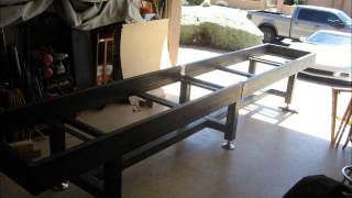 Custom shuffleboard table made from salvaged bowling alley wood and shuffleboard cradle made of steel and powdercoated.