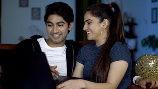 Cute happy couple watching funny videos on a laptop during leisure time in India