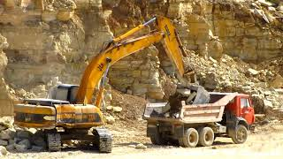 JCB JS330 excavator loads dump trucks in limestone quarry