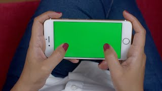 Shot of a woman playing video game on the green screen smart phone