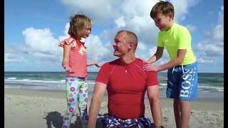 Макс и Катя ищут сюрпризы в песке На пляже с папой