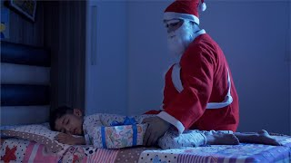 Santa Claus keeping the Christmas gift beside a sleeping boy on Christmas Eve