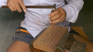 Tarkashi - Craftsman incising the design into the wood with a small chisel and hammer