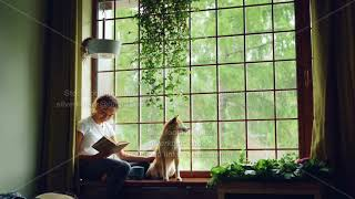 Attractive African American girl student is reading book and stroking her purebred dog sitting on