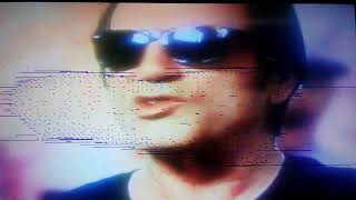 Roy Orbison type guy in wayfarer sunglasses with his hands tied cuffed behind his back