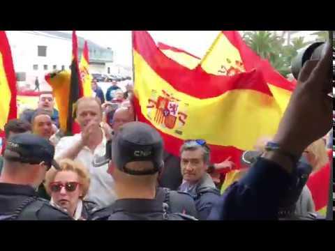 Banderas de España y cánticos contra la independencia a las puertas del acto de Podemos