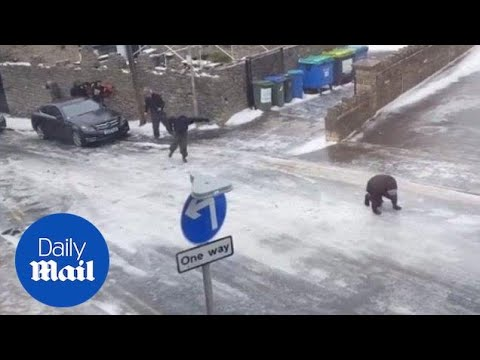 People slipping on an icy road in a town in England - Daily Mail