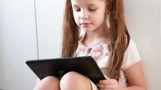 Emotional girl is Playing in Video Games Using Tablet. Portrait of Child with Electronic Gadget