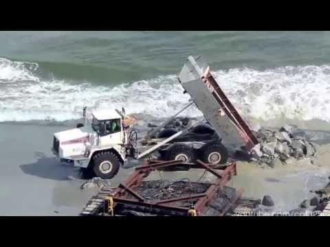 Terex TA35 dump truck dumping rock into ocean