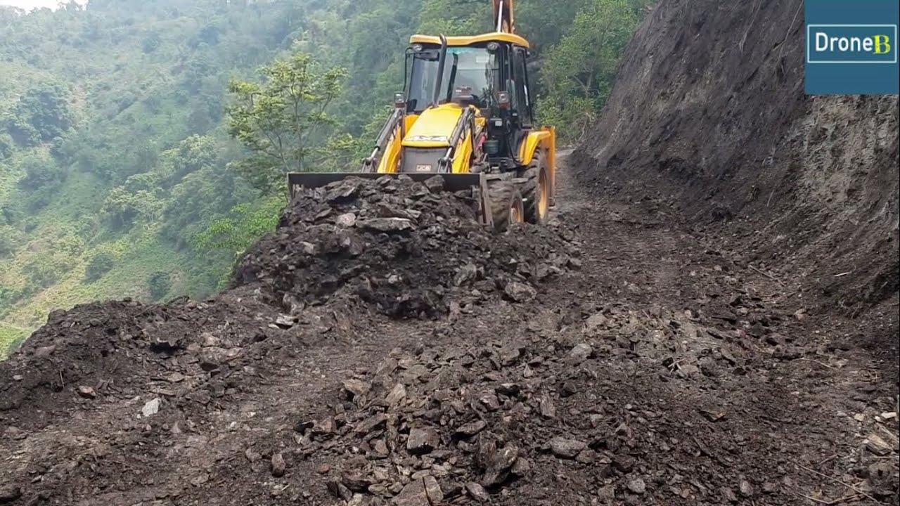 Clearing Hilly Road Dirt after Excavator-Backhoe Loader Working