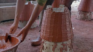 Shot of a potter applying red clay on the cemented planter (Gamla)