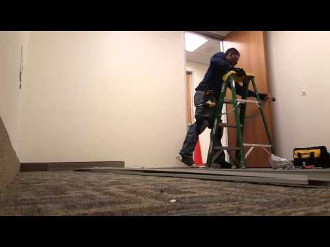 Maintenance Technician removing a commercial office door frame