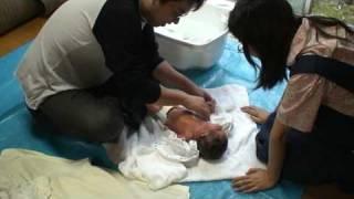 新生児は外で洗います。裸になると不安がるので布をかけたり、何か握ら...