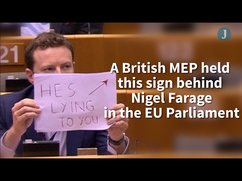 British MEP holds sign behind Nigel Farage in the EU Parliament