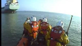 RNLI Lymington Lifeboat alongside Cargo vessel