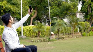 Attractive Indian guy happily taking selfies with his smartphone - technology concept