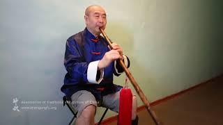 Му Юйчунь играет на бамбуковой флейте сяо китайскую мелодию