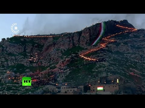 Iraqi Kurds carry torches atop Akre mountain to celebrate Nowruz