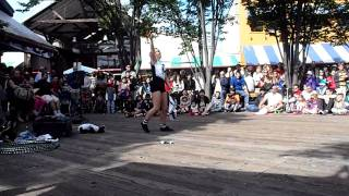 A girl changes her clothes while doing hula hoop tricks.