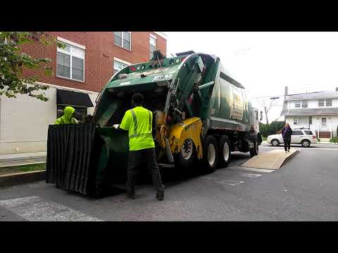 Waste management rear loader collecting garbage