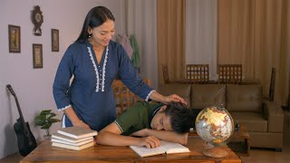 Indian mother caressing her young son while he is napping on his textbook - education concept