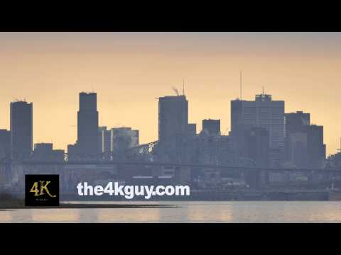 4K UHD - Financial district buildings rising above skyline on a river