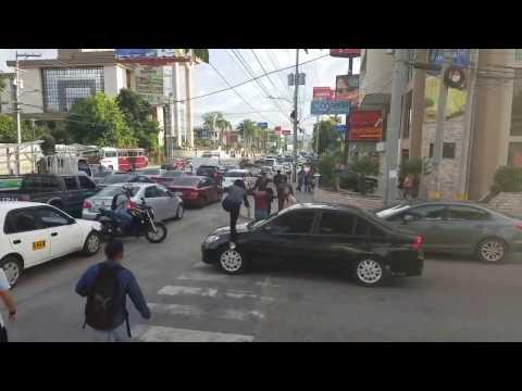 Pedestrians walk over a front car hood that stop in the pedestrian lane