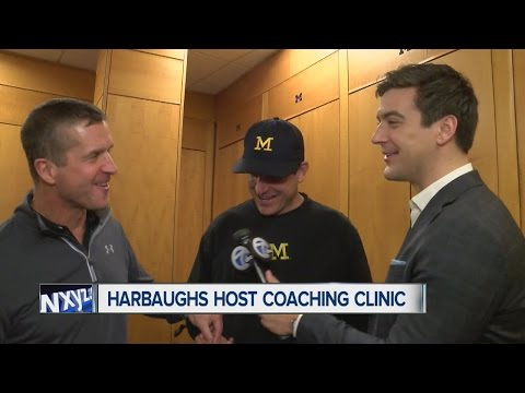 Jim and John Harbaugh jab at each other in conversation with Brad Galli at Michigan Coaching Clinic