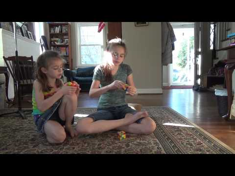 Kid singing the Periodic Table Song while solving Rubik's Cubes