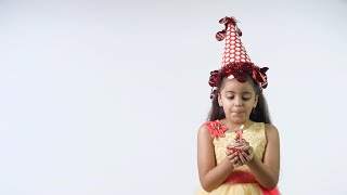 Young sweet girl from India in a beautiful birthday dress and a red party hat - birthday celebration concept
