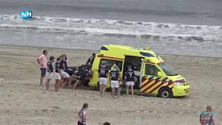 Haarlems rugbyteam duwt ambulance uit het zand op strand