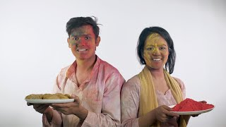 Young friends smeared in colorful Gulal smiling at the camera during Holi festival