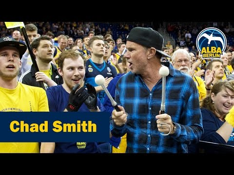 Chad Smith of the Red Hot Chili Peppers drumming with fans at ALBA game