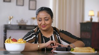 Indian woman in a dilemma and shaking her head to choose between fruits and junk food - Healthy lifestyle