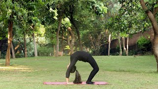 A young girl practicing chakrasana the wheel pose yoga asana outside in a park