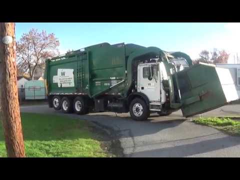 Waste Management Garbage Truck Lifting Up The Dumpster