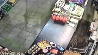 Incredible moment fearless shopkeeper snatches gun out of raider