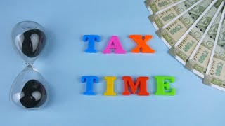 "Top view shot of ""Tax Time"" words beautifully arranged on the blue platform"