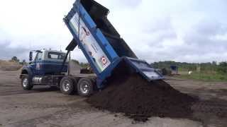 Greely Sand & Gravel unloading a full tandem load of topsoil