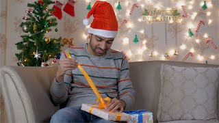 Excited young man opening Christmas presents sitting on a couch